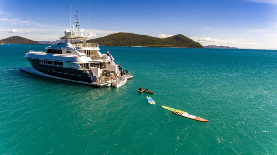 Superyacht anchored in the Whitsundays with Stand Up Paddleboards drifting