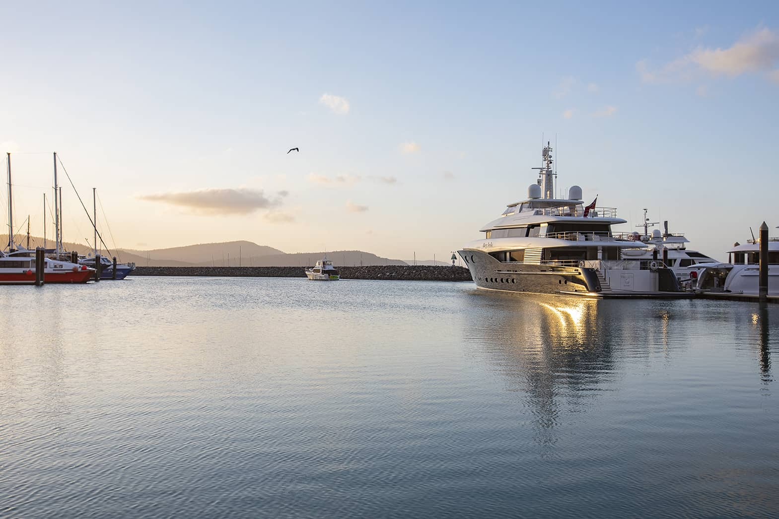 Superyacht vessel berthed at Coral Sea Marina Resort Superyacht arm at sunset, in the Whitsundays