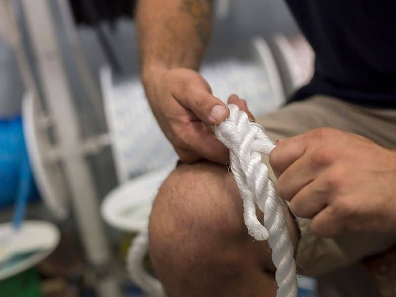 Close up image of man's hands splicing marine rope