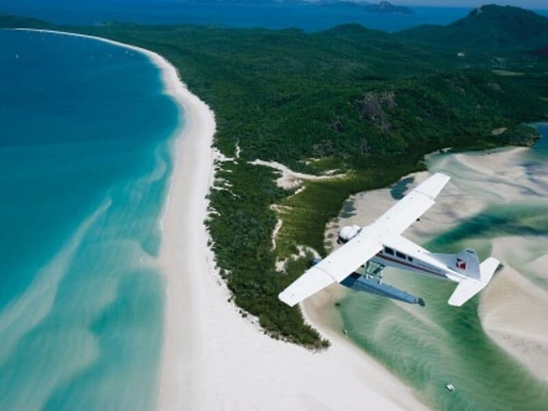 A seaplane flying over Hill Inlet and Whitehaven Beach in the Whitsundays