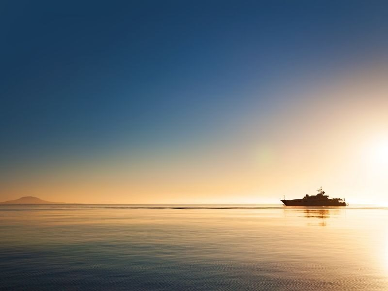 Superyacht cruising on calm ocean at sunset