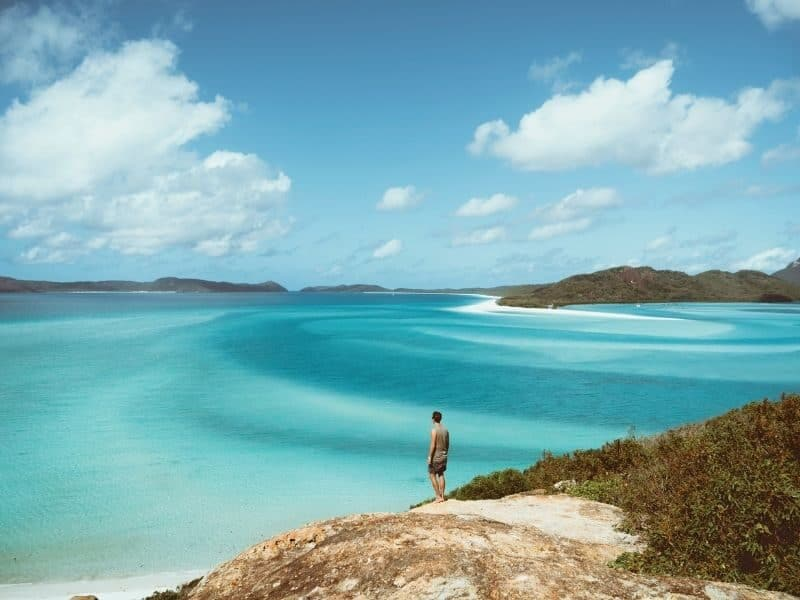 A man standing on a rock at Hill Inlet overlooking the silica sands of Whitehaven Beach in the Whitsundays, Queensland