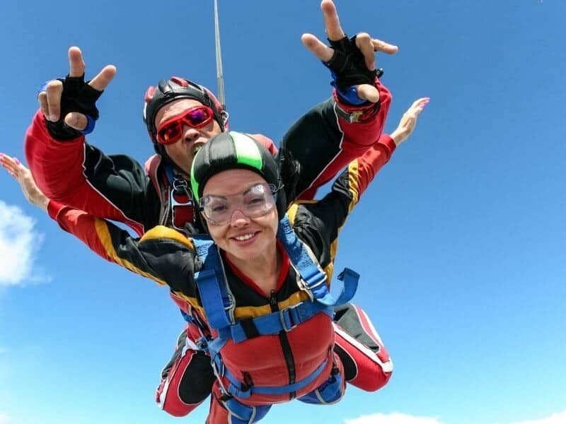 A man and woman tandem skydiving