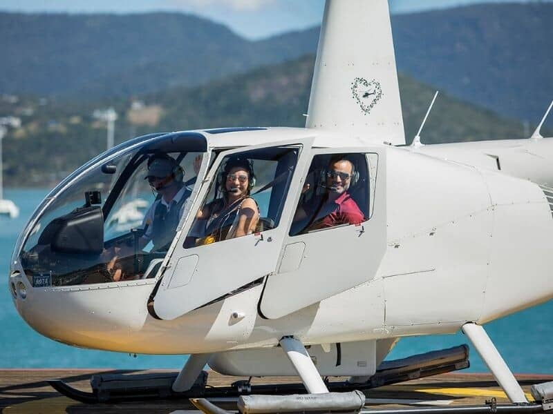 A man and woman using private helicopters to transfer to island resorts from Coral Sea Marina