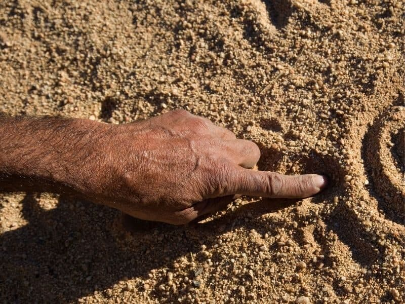 An aboriginal man drawing traditional images in the sand